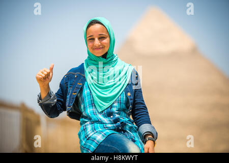 Cairo, Egypt Egyptian woman sitting in front of the Great Pyramids of Giza that are in the background. This particular - Stock Photo