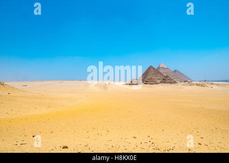 Cairo, Egypt Vast Sahara desert with the three Great pyramids of Giza in the background against a clear blue sky. - Stock Photo