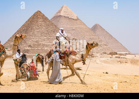 Cairo, Egypt Tourists and camel drivers with their camels walking through the desert with the three Great pyramids - Stock Photo