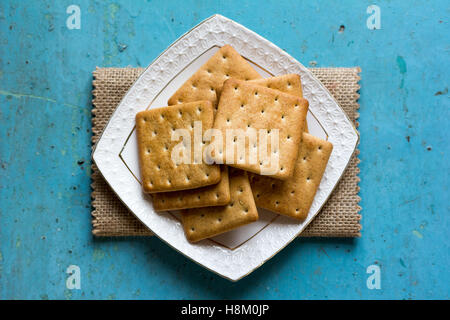 Cracker biscuits in a white ceramic square saucer on linen napkin on old blue background close-up. Top view - Stock Photo