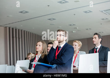 Business people attending seminar in convention center - Stock Photo