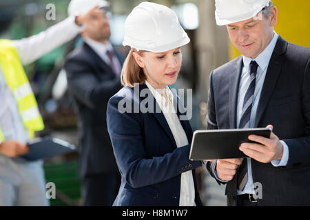 Businessman and businesswoman using digital tablet with colleagues in background at industry - Stock Photo