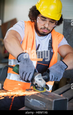 Young manual worker grinding metal in industry - Stock Photo