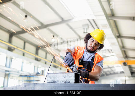 Young manual worker using grinder on metal in factory - Stock Photo
