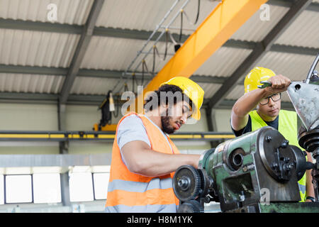 Low angle view of manual workers working on machinery in metal industry - Stock Photo