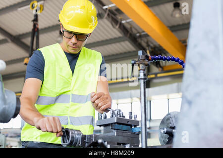 Low angle view of mid adult worker operating machinery in metal industry - Stock Photo