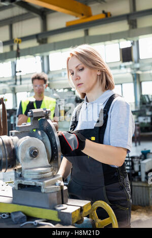 Mature female worker working on machinery with colleague in background at factory - Stock Photo