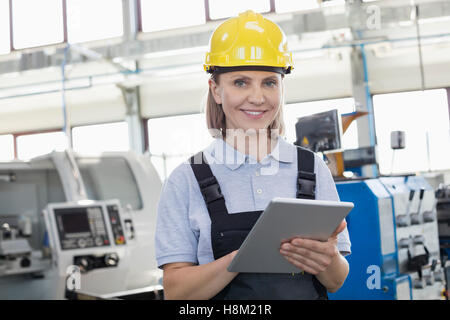 Portrait of smiling female worker using digital tablet in manufacturing industry - Stock Photo