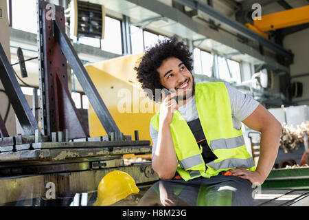 Young manual worker talking on mobile phone in metal industry - Stock Photo