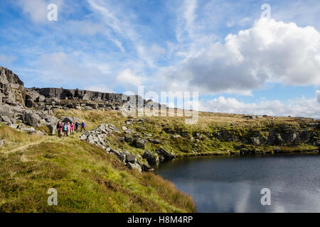 Hikers hiking by a small upland lake in Rhinog mountains of southern Snowdonia National Park. Trawsfynydd, Gwynedd, - Stock Photo