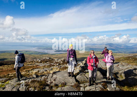 Hikers hiking in Rhinog mountains of southern Snowdonia National Park with a view to Afon Glaslyn river on coast. - Stock Photo