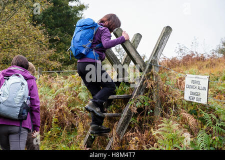 Bilingual 'Danger keep out' sign on a public footpath with hikers climbing a ladder stile over a barbed wire fence. - Stock Photo
