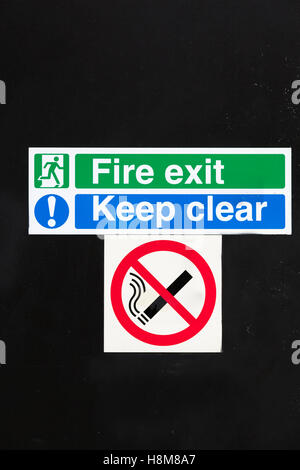 Fire Exit, Keep Clear and No Smoking signs all affixed to a door. - Stock Photo