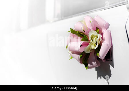 Flower with a pink bow on door handle of a white wedding limousine - Stock Photo