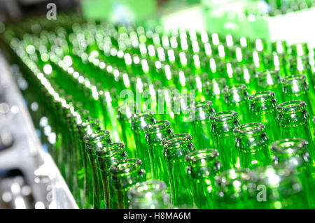 Rows of empty green glass beer bottles on a brewery conveyor - Stock Photo