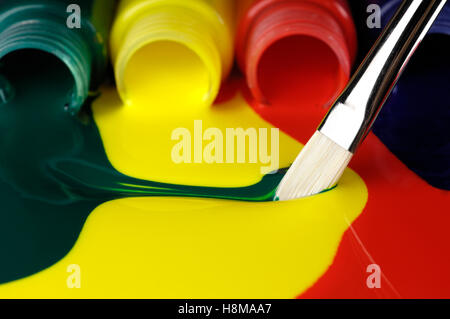 Brush smearing different colors of paint flowing from tubes - Stock Photo