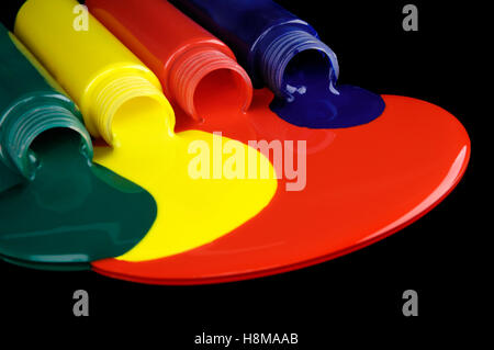 Different colors of paint flowing from tubes - Stock Photo