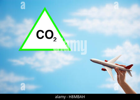 Closeup of woman's hand flying toy plane against cloudy sky with warning CO2 sign - Stock Photo
