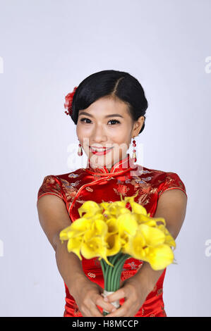 pretty chinese young woman holding a bunch of yellow daffodils - Stock Photo