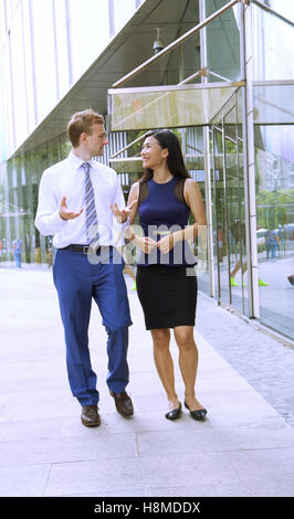 Multi Ethnic Business Team discussing the latest project outside - Stock Photo