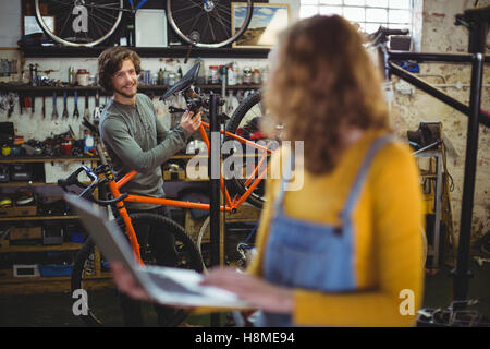 Mechanics interacting while using laptop - Stock Photo