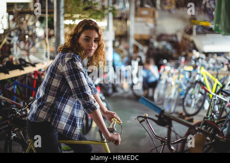 Portrait of beautiful mechanic trying bicycle - Stock Photo