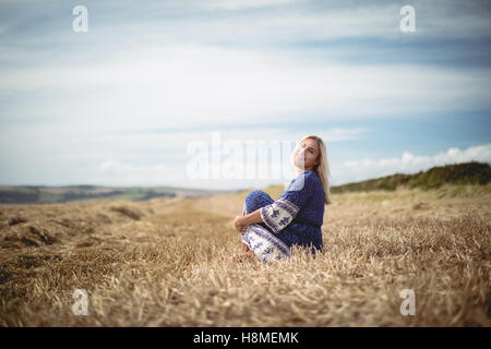 Blonde woman sitting in field - Stock Photo