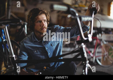 Mechanic examining bicycle - Stock Photo