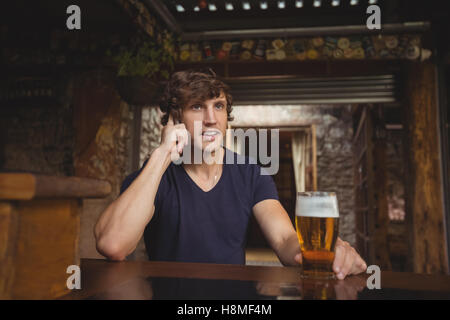 Man talking on mobile phone in bar - Stock Photo