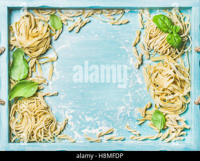 Various homemade fresh uncooked Italian pasta in blue wooden tray - Stock Photo