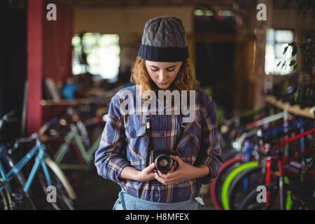 Woman adjusting vintage camera - Stock Photo