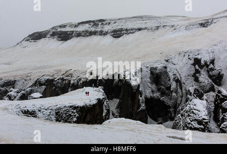 Two people walk on a pathway along the top of Fjaðrárgljúfur Canyon in southeast Iceland - Stock Photo
