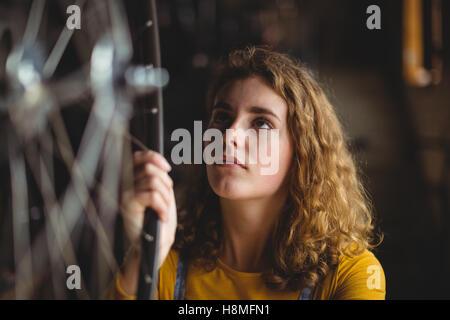 Mechanic examining a bicycle wheel - Stock Photo