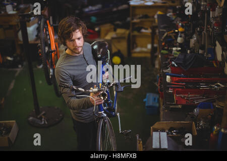 Mechanic carrying a bicycle - Stock Photo