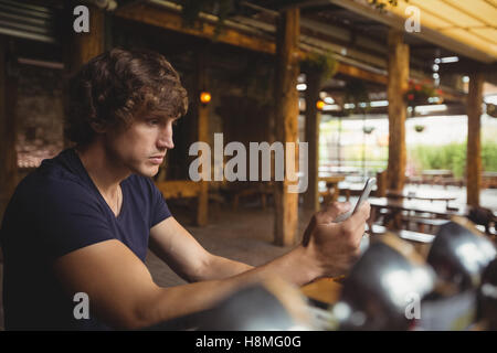 Man using mobile phone in bar counter - Stock Photo