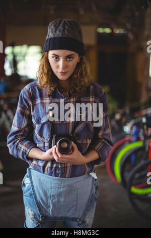 Woman adjusting vintage camera in bicycle shop - Stock Photo