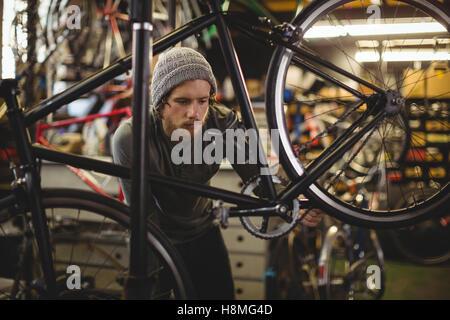 Mechanic examining a bicycle - Stock Photo