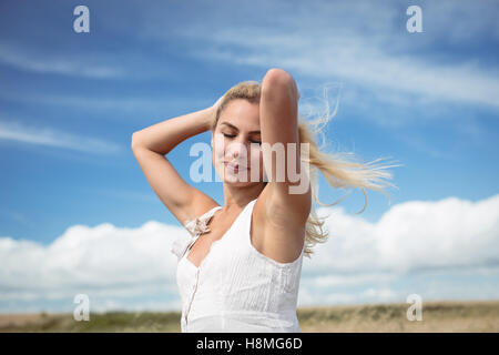 Blonde woman standing in field with hand in hair - Stock Photo