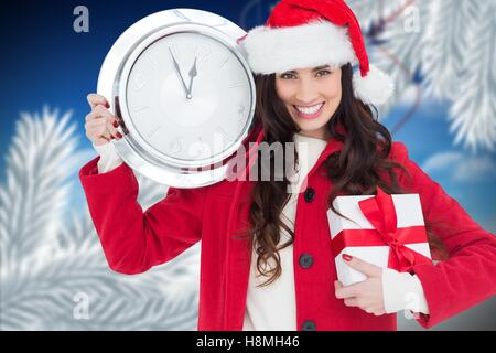Woman in Santa hat holding gift and a wall clock showing few minutes to midnight - Stock Photo