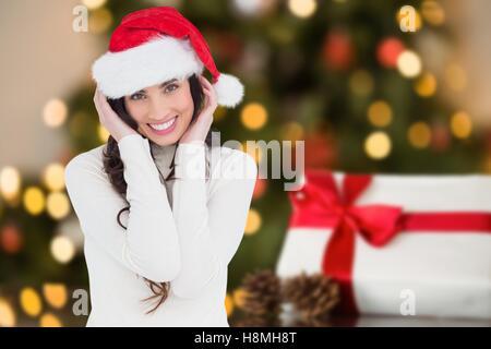 Happy woman in Santa hat smiling at camera - Stock Photo