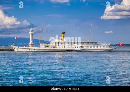Traditional paddle steamer excursion ship with historic Les Paquis Lighthouse on famous Lake Geneva, Geneva, Switzerland - Stock Photo