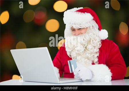 Santa claus doing online shopping with credit card on laptop - Stock Photo