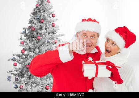 Couple in santa hat holding a gift box near christmas tree - Stock Photo