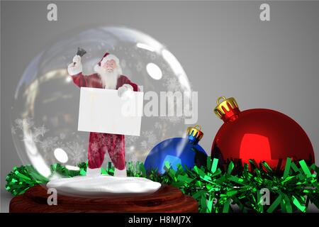 Christmas decoration with santa claus figurine in crystal ball - Stock Photo
