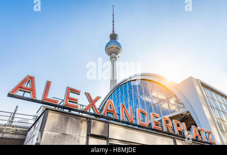 Classic wide-angle view of Alexanderplatz neon sign with famous TV tower and train station at sunset, Berlin, Germany - Stock Photo