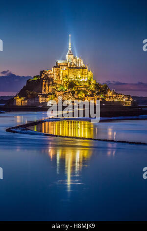 Classic view of famous Le Mont Saint-Michel tidal island in beautiful twilight during blue hour at dusk, Normandy, France