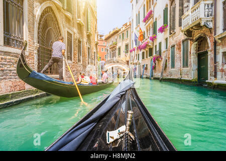 Traditional gondolas on narrow canal in Venice with retro vintage toned filter effect in summer, Veneto, Italy - Stock Photo