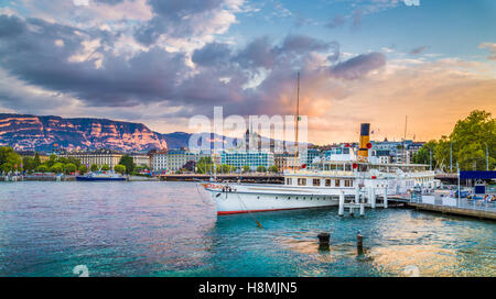 Classic view of the historic city center of Geneva with traditional paddle steamer boat on Lake Geneva at sunset, - Stock Photo