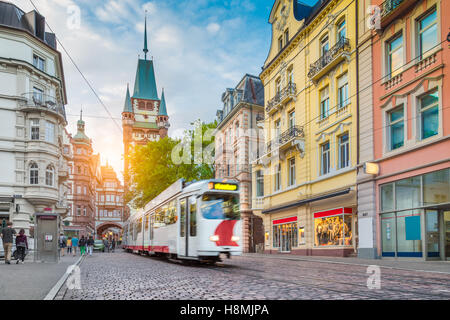 Historic town of Freiburg im Breisgau with traditional tram and famous Martin's Gate at sunset, Baden-Wurttemberg, - Stock Photo