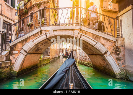 Traditional gondolas on narrow canal in beautiful golden evening light at sunset in summer in Venice, Italy - Stock Photo